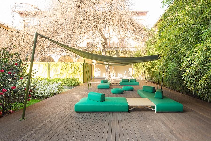 Зелёная софа, пуфики, диваны и деревянный стол на террасе