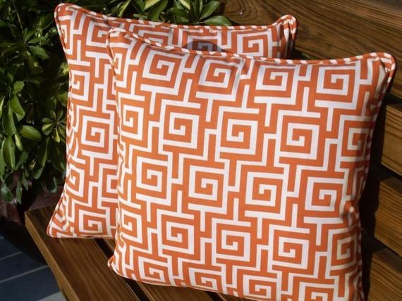 Белые подушки с оранжевым геометрическим узором