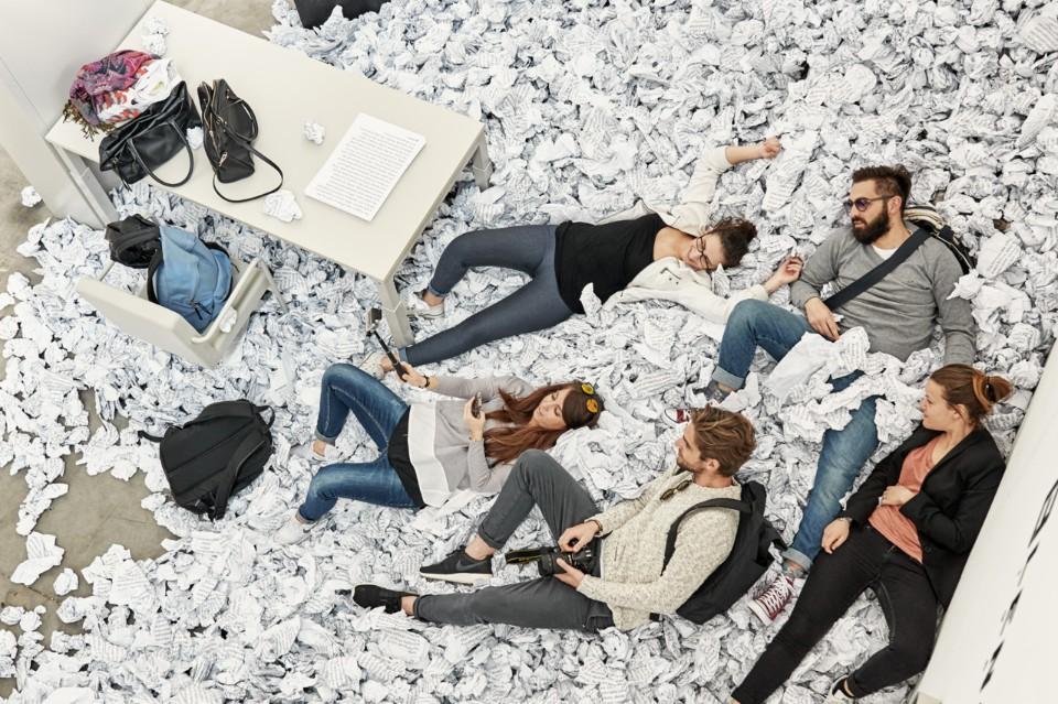 Выставка офисной мебели: люди в груде комков бумаги