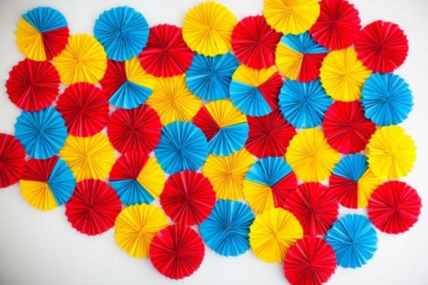 Красивые разноцветные бумажные розетки на однотонной стене
