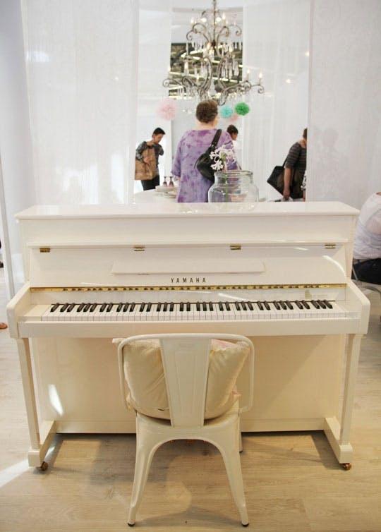 Белое фортепиано на выставке мебели